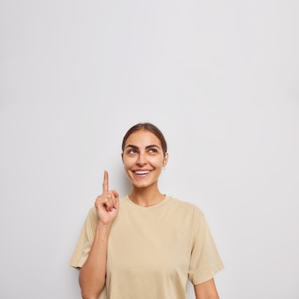 Vertical shot of positive european woman points above with index finger shows advertisement or promo offer dressed in casual t shirt isolated over white wall chooses smth in store