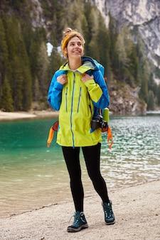 Colpo verticale del viaggiatore positivo passeggia sulla riva vicino al lago di montagna, trasporta la fotocamera