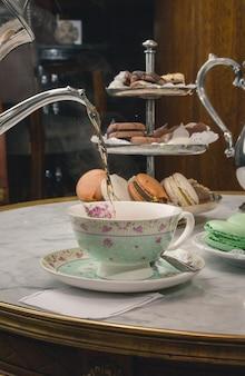 Colpo verticale di un tè di colata in una tazza su un tavolo di marmo con dessert