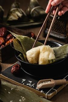 Vertical shot of preparation of rice dumplings with banana leaves