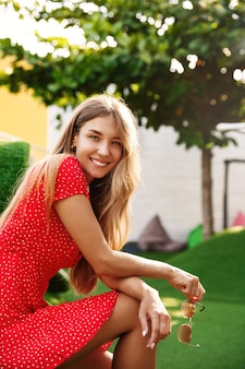 Vertical shot of pretty blond girl sitting in green park on a summer day, wearing a dress and holding sunglasses, turn at camera to smile