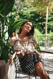 Vertical shot of pretty brunette woman sitting in shadow of tropical palm leaves.
