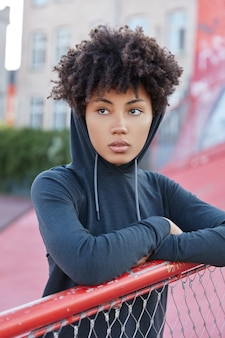 Vertical shot of pretty dark skinned woman with afro haircut, dressed in hood