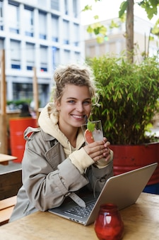 Vertical shot of a pretty smiling woman looking happy while drinking a cocktail, sitting outdoor table coffee shop, using a laptop.