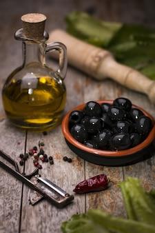 Colpo verticale di prodotti: olio d'oliva, olive, pepe
