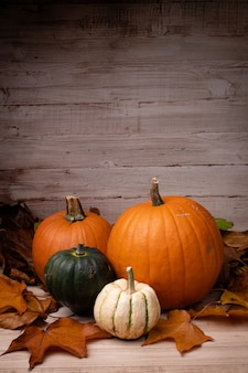 Vertical shot of pumpkins surrounded by leaves with a wooden background for halloween