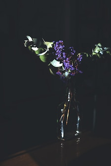 Colpo verticale di un fiore viola in un barattolo di vetro con una parete scura