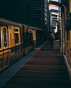 Vertical shot of a railway station with the train during the sunrise