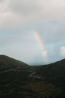 Vertical shot of a rainbow in the mountain valley with a cloudy sky
