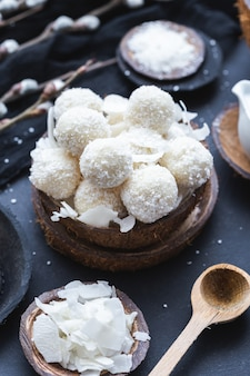 Vertical shot of raw raffaello in a wooden bowl with coconut chunks and a wooden spoon