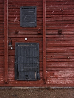Vertical shot of a red wooden wall with gray wooden doors in winter