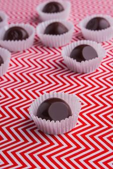Вертикальный выстрел светоотражающие коричневые шоколадные конфеты крупным планом
