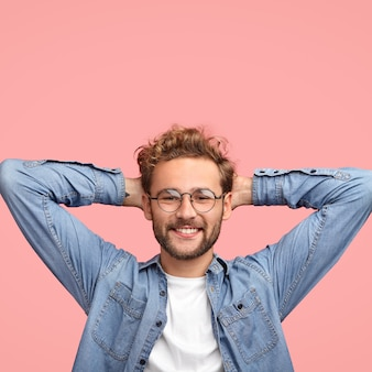 Colpo verticale dell'uomo spensierato rilassato tiene le mani dietro la testa, ha un'espressione positiva, sorride piacevolmente, ascolta qualcosa con interesse, vestito con una camicia alla moda, isolato sopra il muro rosa
