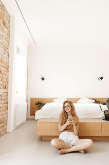Vertical shot of relaxed and happy young woman sitting on floor near bed, using mobile phone and smiling