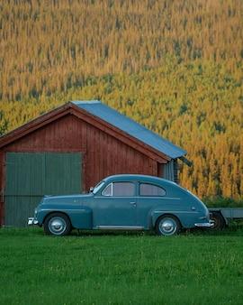 Vertical shot of a retro car near a house