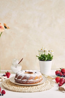 Vertical shot of a ring cake with fruits and powder on a white table with white