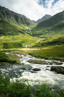 Vertical shot of a river surrounded by the mountains and meadows in scotland