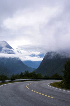Vertical shot of a road surrounded by high rocky mountains covered with white clouds