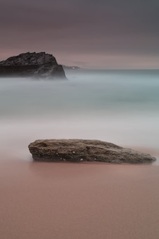 Vertical shot of a rock at the coast under the dark purple sky