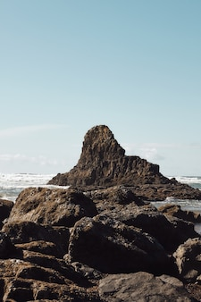 Vertical shot of rocks at the coastline of the pacific northwest in cannon beach, oregon