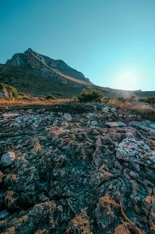 Colpo verticale delle rocce vicino ad un campo erboso asciutto con la montagna e un chiaro cielo blu
