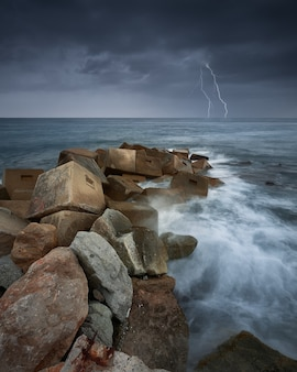 Vertical shot of rocks in the sea during a thunderstorm and lightning