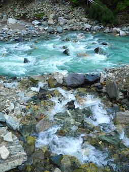 Colpo verticale di rocce in un ruscello che scorre acqua