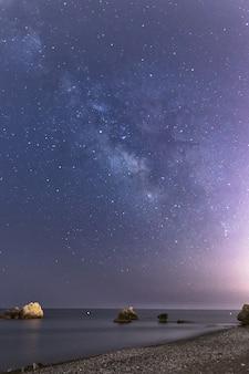 Ripresa verticale di rocce sulla spiaggia di torre de la sal in spagna in una bella notte