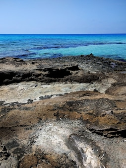 Vertical shot of the rocky beach in formentera, spain
