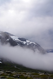 Vertical shot of rocky mountains covered in the snow and fog in norway