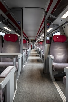 Vertical shot of the rows of red and grey seats inside an empty train