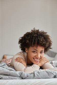 Colpo verticale di soddisfatta signora dall'aspetto piacevole con i capelli ricci sorriso a trentadue denti, giace sullo stomaco in un letto comodo, ha un fine settimana, gode di comfort e accogliente atmosfera domestica. persone e concetto di riposo