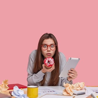 Colpo verticale di uno studente universitario spaventato guarda attraverso gli occhiali, tiene in mano una gustosa ciambella, porta il touchpad aggiornato, ha molti documenti sul tavolo