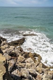 Colpo verticale del mare circondato dalle rocce sotto la luce del sole durante il giorno