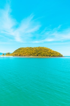 Vertical shot of the sea with an island covered in trees under a blue sky