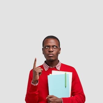 Vertical shot of serious black man has thoughtful expression, dressed in red sweater, points with index finger on ceiling
