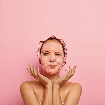 Vertical shot of serious female model with facial sheet mask, spreads palms near face, has beauty routine at home in evening, wears bath cap, stands naked, isolated on pink wall, blank space above