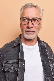 Vertical shot of serious grey haired man with beard concentrated away wears transparent glasses