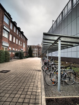 Vertical shot of several bicycles parked next to a building