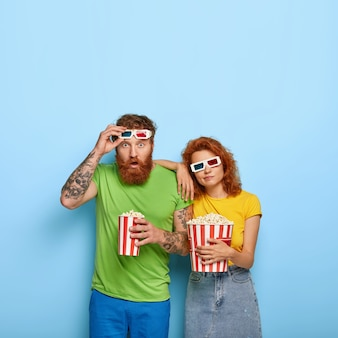 Vertical shot of shocked man stares with surprise, takes off 3d glasses, sad bored woman leans at shoulder, spend free time at cinema, eat tasty popcorn, pose indoor. people and entertainment