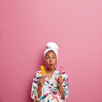 Vertical shot of shocked mixed race woman looking above, holds breath, holds two yummy ice creams of stawberry and mango taste, wears towel and robe after taking bath, has unhealthy nutrition