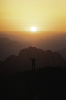 Vertical shot of the silhouette of a male tourist in top of the mountain looking at the sunset