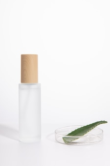 Inquadratura verticale di una singola bottiglia per la cura della pelle accanto a un piatto con aloe ver