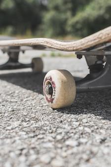Ripresa verticale di uno skateboard a terra sotto la luce del sole