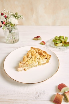 Colpo verticale di una fetta di torta crostata croccante rhabarbar e alcuni ingredienti su un piatto bianco