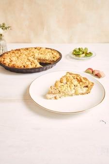 Ripresa verticale di una fetta di torta di rhabarbar croccante su un piatto bianco con alcuni frutti