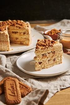 Colpo verticale di una fetta di torta di biscotto di loto delizioso con caramello con i biscotti sul tavolo