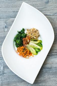 Colpo verticale delle verdure e della tagliatella affettate su un piatto moderno bianco