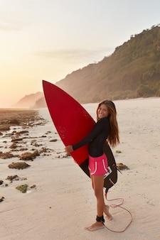 縦長のスリムで魅力的な女性は長い髪をしていて、サーフィン用のショートパンツを着ています