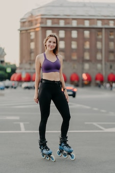 Vertical shot of slim woman wears cropped top and trousers poses on rollers enjoys free time has healthy body enjoys rollerblading